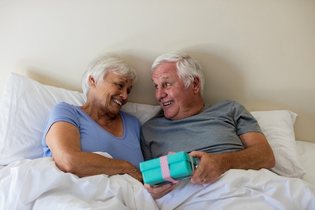 Último homem dando um presente surpresa para uma mulher no quarto em casa