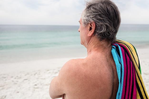 Último homem de pé na praia com uma toalha no ombro