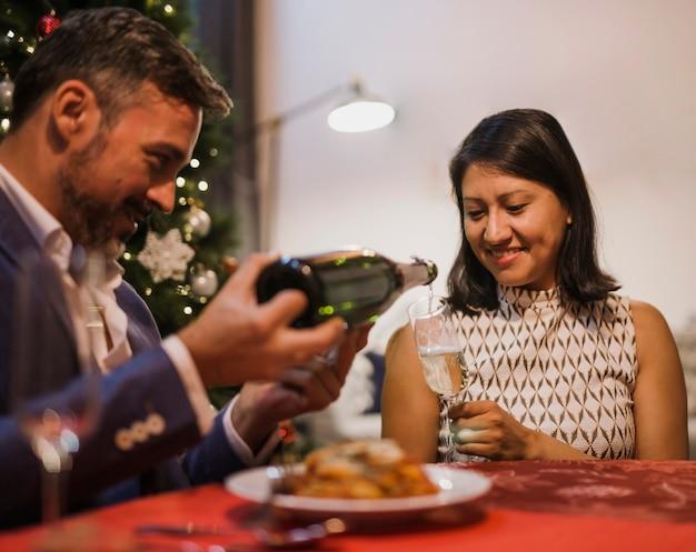 Último homem derramando champanhe para sua esposa