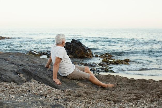 Último homem descansando na praia e admirando o oceano