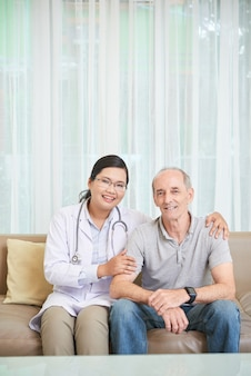 Último homem e médico sentado no sofá na sala de estar