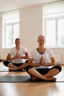 Último homem e mulher fazendo yoga