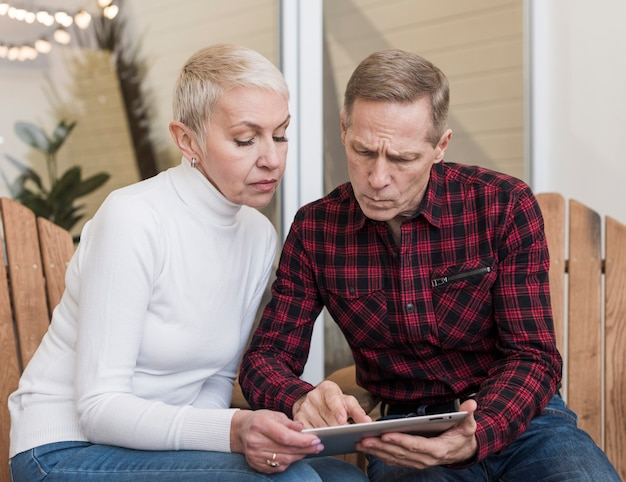 Último homem e mulher olhando juntos em um tablet