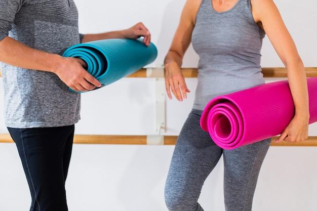 Último homem e mulher segurando tapetes de ioga