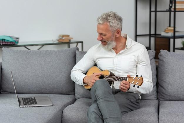 Último homem em casa estudando aulas de ukulele no laptop