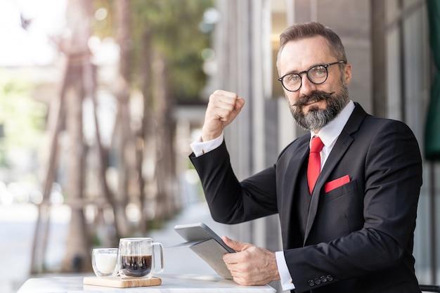 Último homem em terno de negócio inteligente pensando e sentado na mesa de centro ao ar livre.