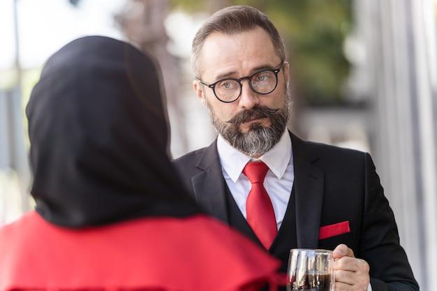 Último homem em um terno de negócio inteligente, falando com as pessoas e sentado na mesa de centro ao ar livre.