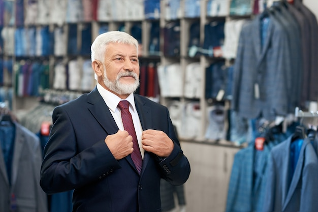 Último homem escolhendo roupas elegantes na loja para homens.
