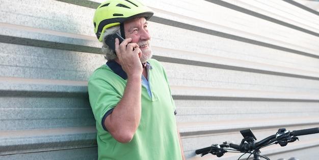 Último homem falando ao ar livre no celular, descansando perto de sua bicicleta com um capacete protetor