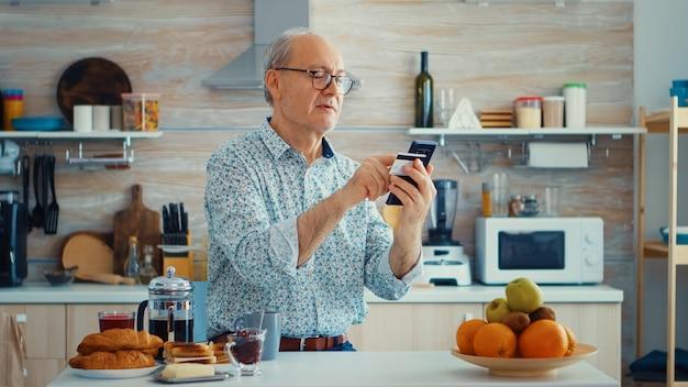Último homem fazendo transações on-line usando o aplicativo de telefone para pagamento durante o café da manhã na cozinha. idoso aposentado que usa o pagamento pela internet, compra do banco doméstico com tecnologia moderna
