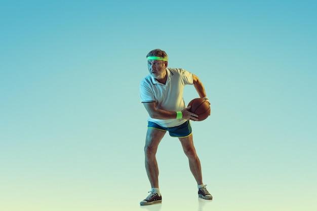 Último homem jogando basquete em fundo gradiente em luz de néon. modelo masculino caucasiano em ótima forma permanece ativo, esportivo.
