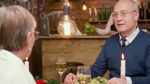Último homem olhando curioso para sua esposa durante o encontro. casal romantico. copo de vinho. comendo juntos.