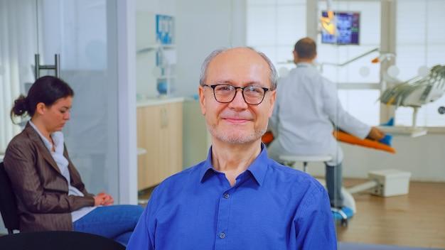 Último homem olhando para a câmera enquanto o médico examinando o paciente em segundo plano. homem idoso sorrindo na webcam, sentado na cadeira na sala de espera da clínica de estomatologia, assistente digitando no pc