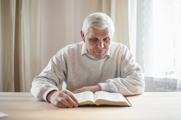 Último homem orando, lendo uma velha bíblia nas mãos.