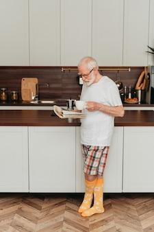 Último homem relaxando em casa, lendo jornal e tomando café da manhã