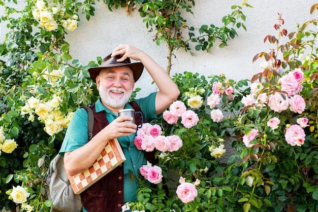 Último homem relaxando em seu jardim. jardineiro sênior está apreciando seu trabalho no jardim.