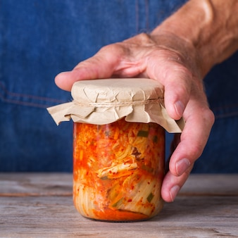 Último homem segurando nas mãos salada de repolho kimchi coreano tradicional orgânica caseira em uma jarra de vidro sobre uma mesa de madeira. conceito de comida saudável intestinal com conservas vegetarianas fermentadas e veganos