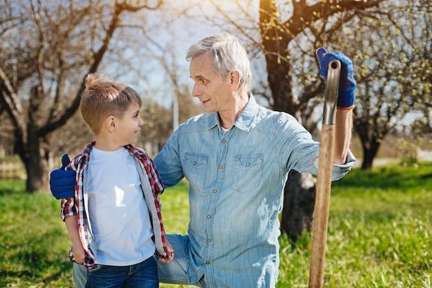 Último homem segurando uma pá e apoiado no joelho enquanto abraça o netinho em um dia ensolarado