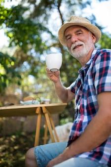 Último homem tomando café no jardim