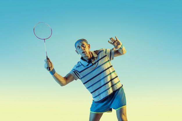 Último homem vestindo roupas esportivas jogando badminton em fundo gradiente, luz de néon. modelo masculino caucasiano em ótima forma permanece ativo. conceito de esporte, atividade, movimento, bem-estar, confiança.