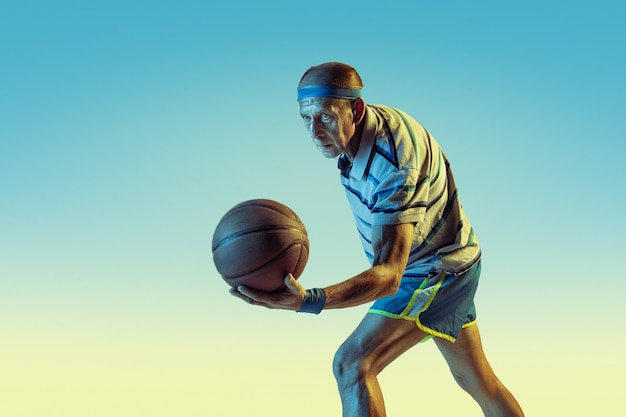 Último homem vestindo roupas esportivas jogando basquete em fundo gradiente, luz de néon. modelo masculino caucasiano em ótima forma permanece ativo. conceito de esporte, atividade, movimento, bem-estar, confiança.