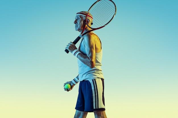 Último homem vestindo roupas esportivas jogando tênis em fundo gradiente, luz de néon. o modelo masculino caucasiano em ótima forma permanece ativo, esportivo. conceito de esporte, atividade, movimento, bem-estar, confiança.