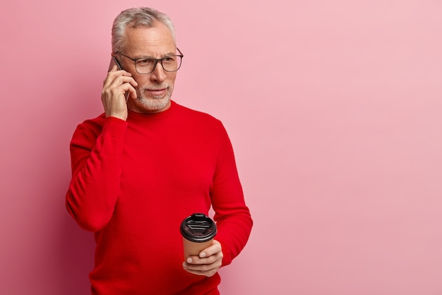 Último homem vestindo um suéter vermelho e falando ao telefone