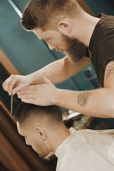 Últimos passos de estilo. tiro vertical de um barbeiro barbudo estilizando seu cliente em uma barbearia