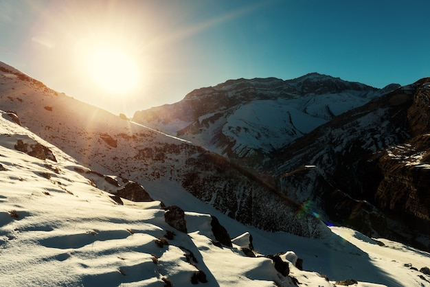 Últimos raios de sol no pico de uma montanha nevada