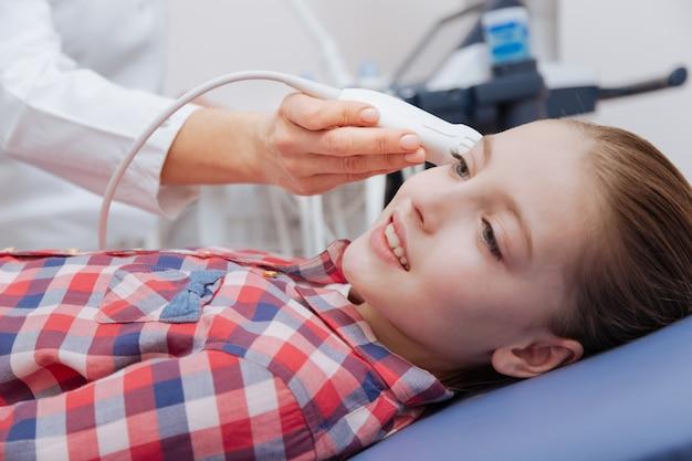 Ultrassonografista atencioso e otimista trabalhando na clínica enquanto fornece monitoramento de vasos ultrassônicos na cabeça e usa máquina de ultrassom