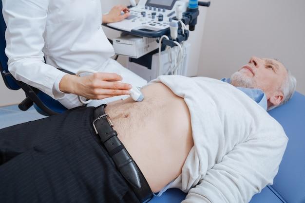 Ultrassonografista inteligente e útil profissional trabalhando na clínica enquanto fornece varredura ultrassônica do abdômen e usa sonda linear de ultrassom