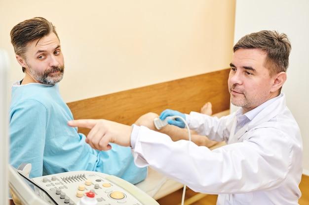 Ultrassonografista maduro apontando para o monitor enquanto explica a imagem do ultrassom ao paciente na clínica