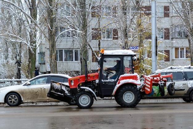 Ulyanovsk, rússia - 2 de dezembro de 2019: passeios de trator de neve em uma estrada molhada e com neve. primeira neve. snowblower.