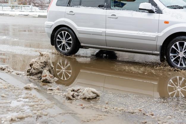 Ulyanovsk, rússia - 20 de fevereiro de 2020: salpicos de água sob as rodas de um veículo em movimento através de poças sujas de neve derretida. águas da inundação após uma nevasca.