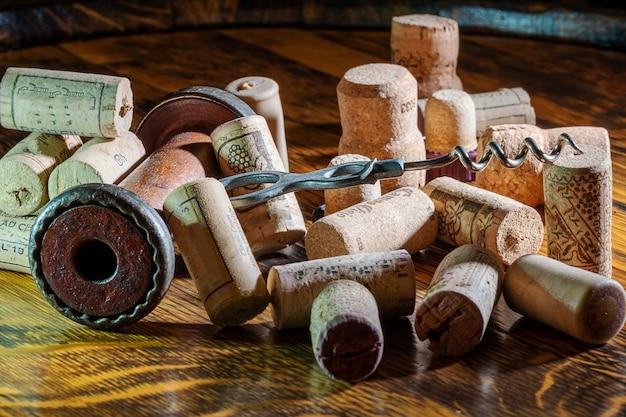 Um abridor de garrafas tipo parafuso velho e rolhas em cima da mesa.