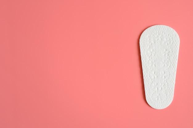Um absorvente higiênico menstrual diário descartável feminino puro ou um guardanapo rosa