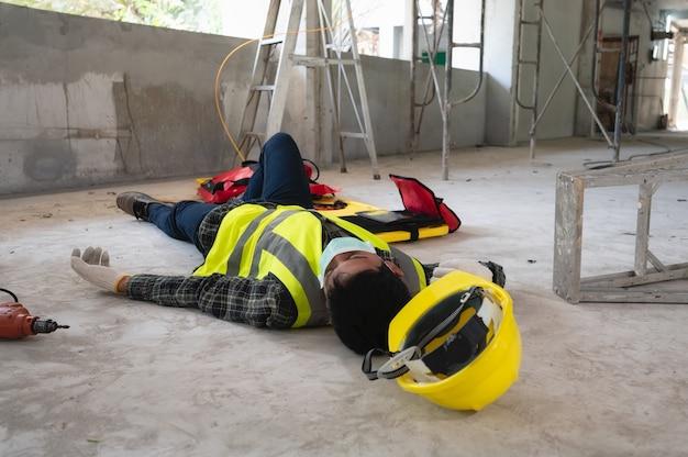 Um acidente de um trabalhador no canteiro de obras. eles auxiliam os feridos nas primárias. foco de seleção em uma pessoa ferida.