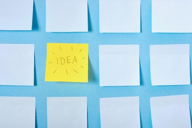 Um adesivo amarelo com a ideia de inscrição entre o conjunto de adesivos de papel azul claro em uma superfície azul