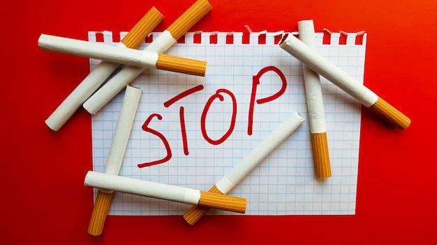 Um adesivo que diz pare está em um maço de cigarros. dia mundial sem tabaco. parar de fumar. lute com cigarros.