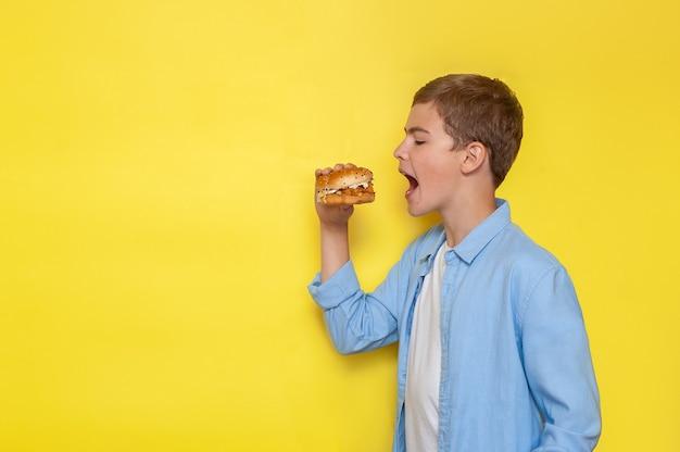Um adolescente de camisa azul morde um hambúrguer