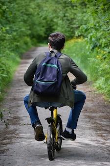 Um adolescente de cerca de 14 anos anda de bicicleta infantil por um caminho na floresta com uma mochila, as pernas afastadas em uma pose engraçada. vista traseira