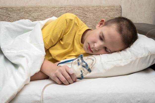 Um adolescente doente em casa na cama com uma máscara de respiração está deitado de lado no sofá. em uma camiseta amarela.