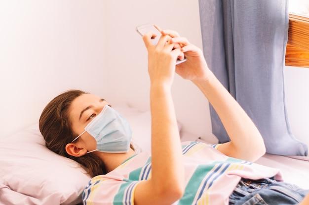 Um adolescente em quarentena com mensagens de texto de máscara facial com smartphone, conceito de coronavírus.