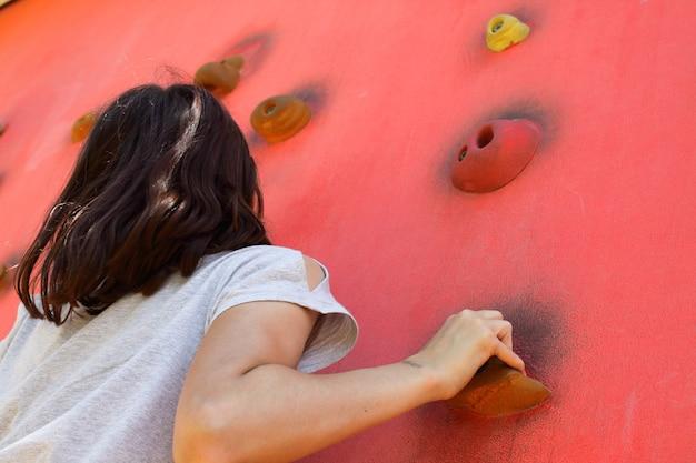Um adolescente escala uma parede de escalada