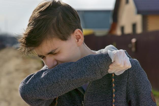 Um adolescente espirra na rua, se escondendo atrás da mão