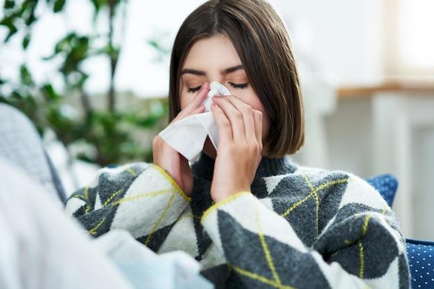 Um adolescente espirrando em um lenço de papel na sala de estar