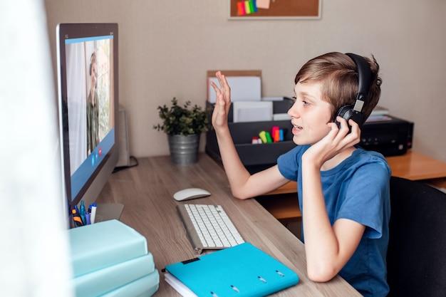 Um adolescente se comunica com parentes por meio de uma videoconferência com câmera da web no computador em casa.