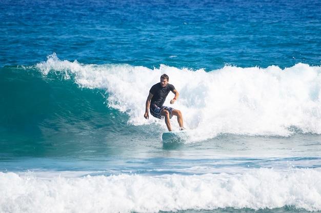 Um adulto monta uma onda em uma prancha de surf. surf.