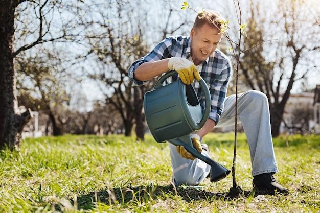 Um adulto sorridente, apoiado em um joelho, despejando em seu jardim uma árvore recém-plantada com um regador verde