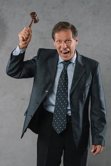 Um advogado masculino maduro irritado que bate com o martelo contra o fundo textured cinzento